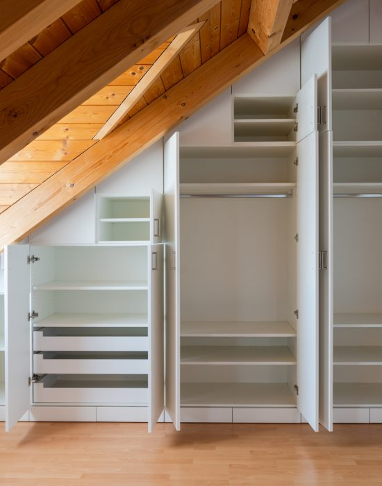 A interior view of a custom-made closet with open doors built into a master bedroom with a sloping roof