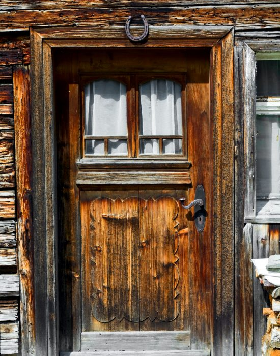 Old wooden door and facade of grunge and old Bavarian house in Allgäu. Over door is horse shoe for lucky days.